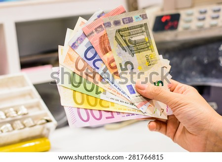 Exchange euro currency,money at counter in the bank branch on colorful banknotes - stock photo