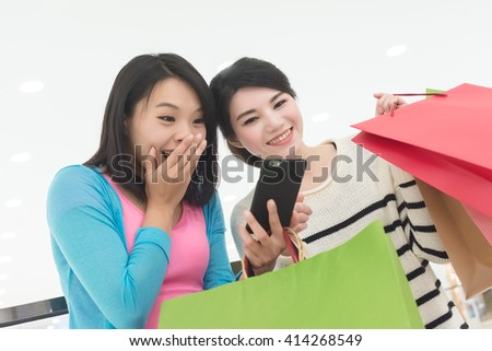 Excite women go shopping and use a smartphone in department store - stock photo
