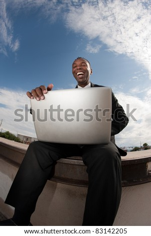 Excited African-American businessman relaxes while working on his laptop - stock photo