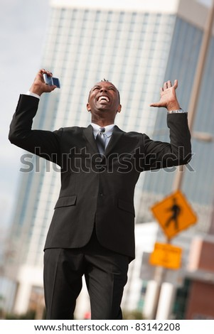 Excited African-American businessman with raised arms - stock photo