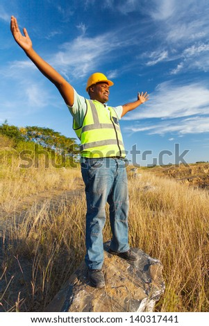 excited african construction worker with arms outstretched outdoors - stock photo