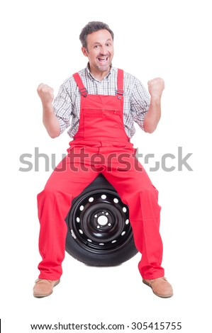 Excited and enthusiastic mechanic shouting for joy with arms up sitting on a tire - stock photo
