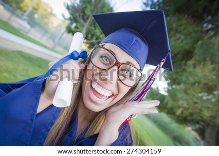 Excited and Expressive Young Woman Holding Diploma in Cap and Gown Outdoors. - stock photo