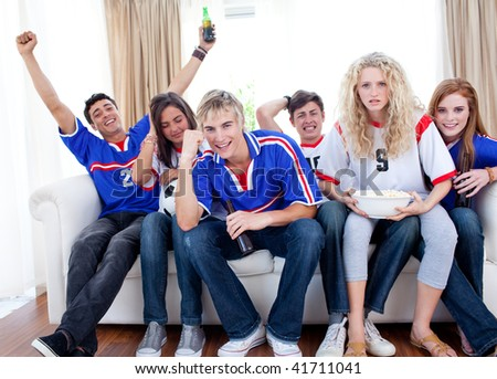 Excited and happy teenagers watching a football match in the living-room - stock photo