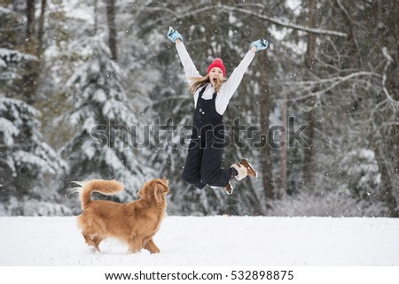 Excited and happy young girl jumping in the air with her golden