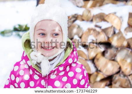 Excited and smiling five years old caucasian child girl looking at snow outdoor during winter. Close up portrait - happy careless childhood. - stock photo