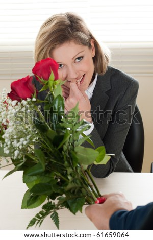 Excited and surprised businesswoman receiving red roses - Valentine's day, Birthday or Anniversary - stock photo