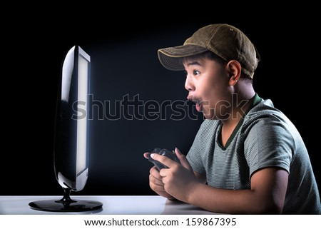 Excited asian boy playing computer game with expressing face - stock photo