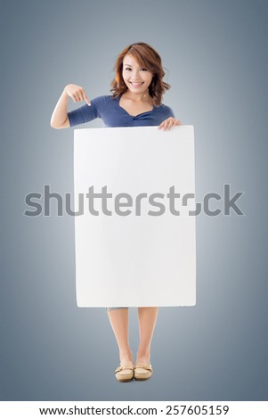 Excited Asian girl hold a blank board, full length portrait isolated. - stock photo