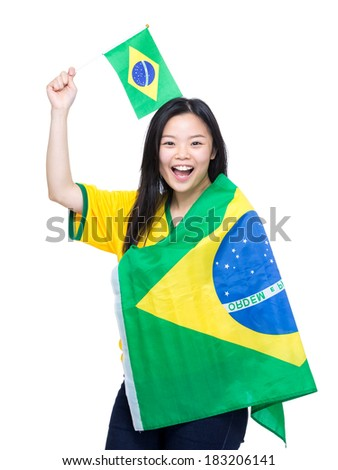 Excited asian woman holding and draping with Brazil flag