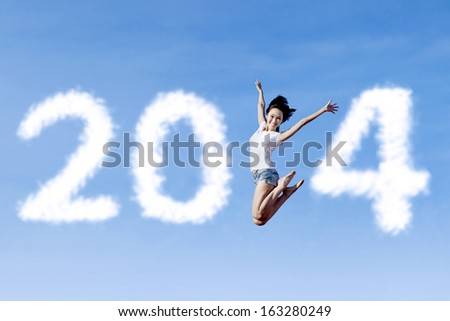 Excited asian woman is jumping with new year 2014 on the clear sky - stock photo