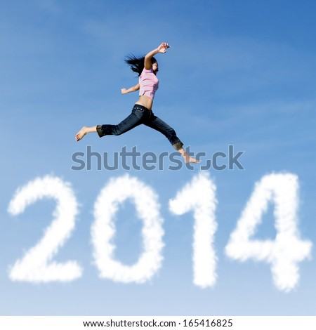 Excited asian woman is jumping with new year 2014 on the sky - stock photo