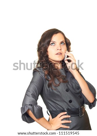 excited attractive girl in a gray business dress and long brown curly hair talking on the phone and looking up. Isolated on white background