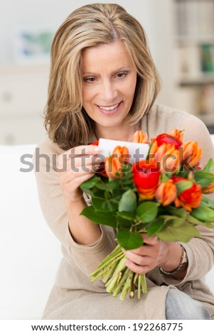 Excited attractive middle-aged blond woman reading the note on a bouquet of fresh colorful orange flowers given to her as a gift - stock photo