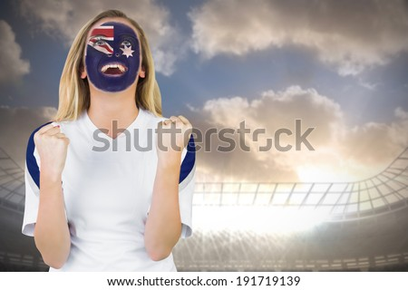 Excited australia fan in face paint cheering against large football stadium under cloudy blue sky - stock photo