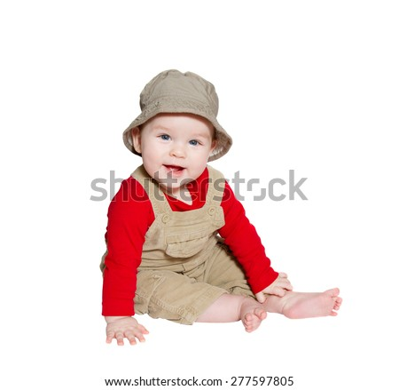 Excited baby explorer/farmer sits on white background, looking at camera - stock photo