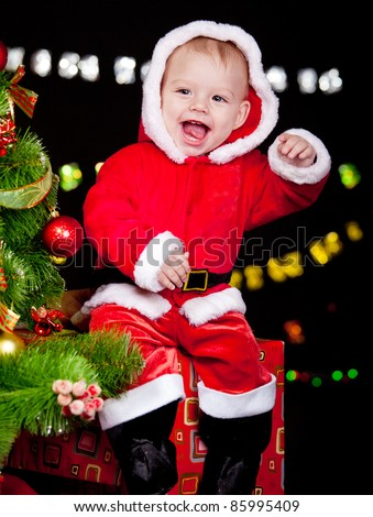 Excited baby in red Christmas costume sitting on present box - stock photo