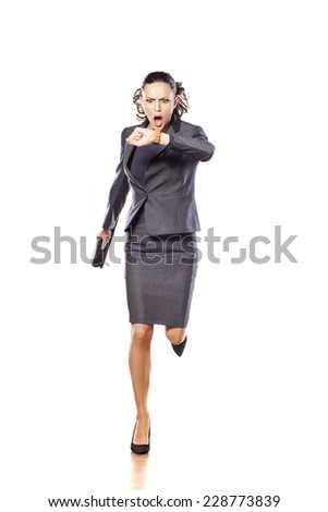 Excited beautiful business woman running and looking at her watch - stock photo