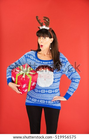 Excited beautiful single woman in tacky knitted sweater and antlers tiara holding a large Christmas gift