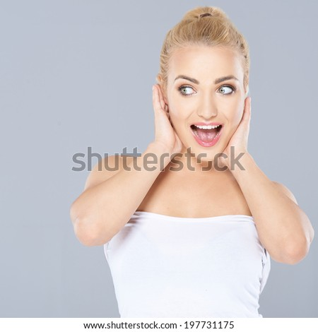 Excited beautiful young blond woman with an expression of amazement holding her hands to her cheeks and looking sideways to the left - stock photo