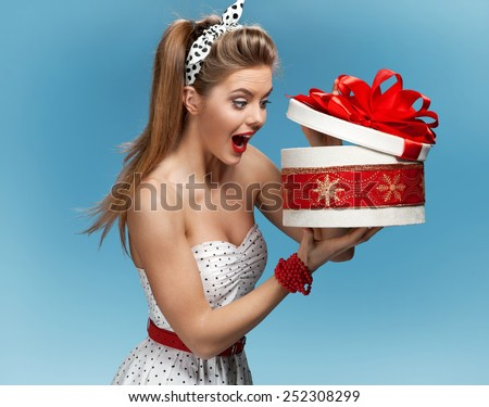 Excited birthday girl opening surprise gift with a look of amazement and shock / set photos of beautiful young retro pinup woman on blue background  - stock photo