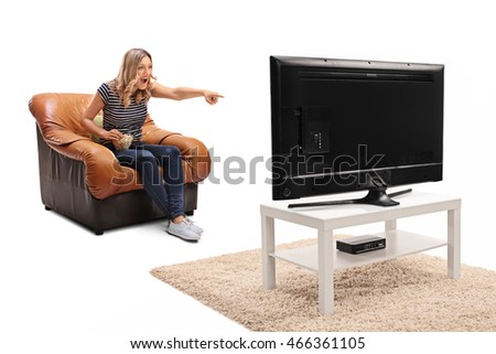 Excited blond woman seated on an armchair watching something funny on TV isolated on white background