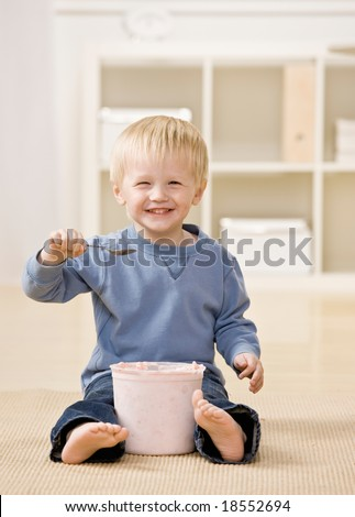 Excited boy eats ice cream from tub