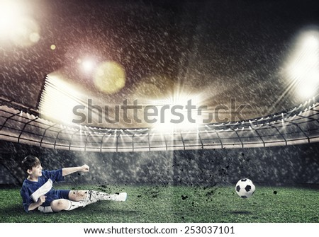 Excited boy football player at stadium kicking ball - stock photo