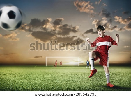 Excited boy football player at stadium kicking ball