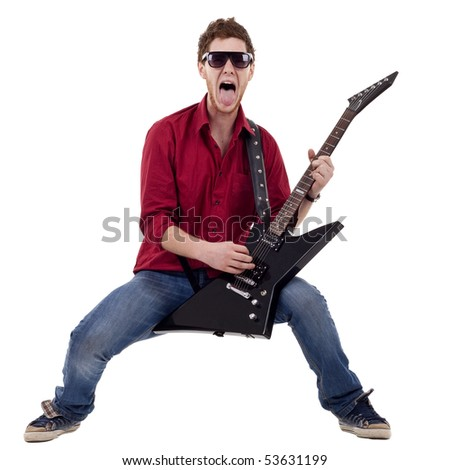 excited boy playing a guitar and sticking his tongue out while playing - stock photo
