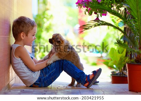 excited boy playing with beloved puppy - stock photo