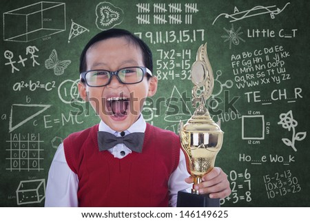 Excited boy screaming while holding trophy in class - stock photo