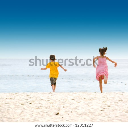 Excited brother and sister running on soft sandy beach towards the sea - stock photo