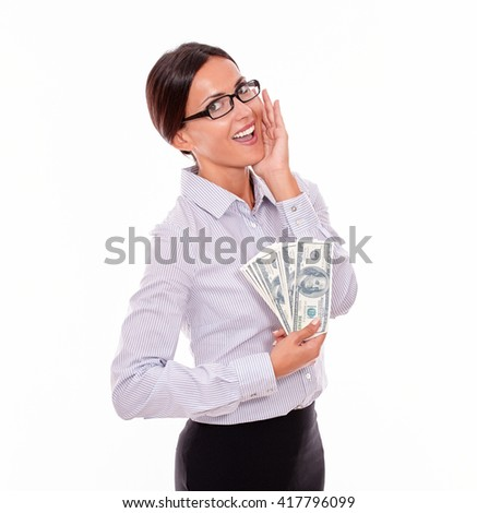 Excited brunette businesswoman holding money with an impressed gesture of her hand to her face while wearing her straight hair back and a button down shirt from the waist up on a white background - stock photo