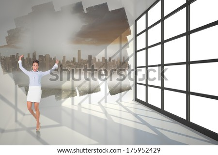 Excited brunette businesswoman jumping and cheering against abstract screen in room showing cityscape - stock photo
