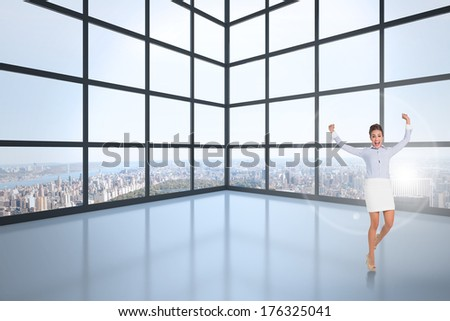 Excited brunette businesswoman jumping and cheering against room with large windows showing city - stock photo