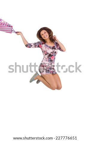 Excited brunette jumping while holding shopping bag on white background - stock photo