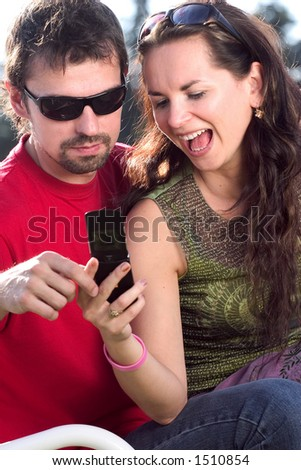 Excited brunette looking at the mobile phone together with her boyfriend.