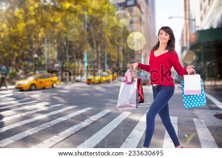 Excited brunette with shopping bags against blurry new york street - stock photo