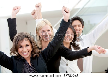 Excited business group at the office with arms up - stock photo