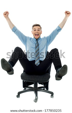 Excited business man with arms raised while sitting - stock photo