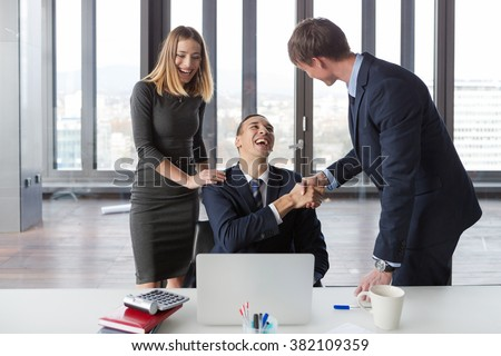 Excited business people in modern office working on project. - stock photo