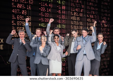 Excited business team cheering at camera against stocks and shares - stock photo