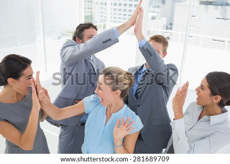 Excited business team cheering in the office - stock photo