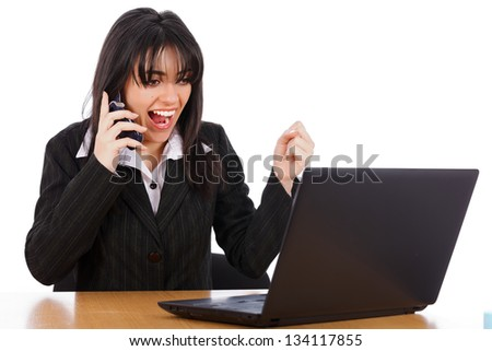 Excited business woman on the phone looking at laptop.