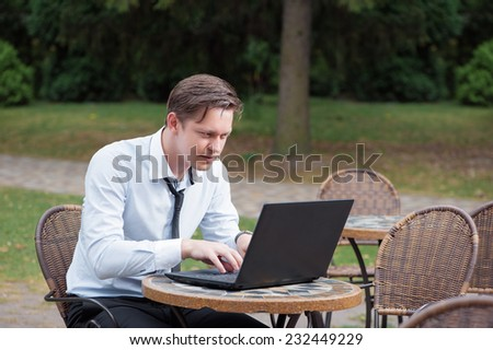 Excited businessman. Attractive young tired caucasian man in formal shirt and tie working on laptop while sitting at the table outdoors - stock photo