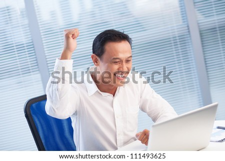 Excited businessman enjoying success at his table - stock photo