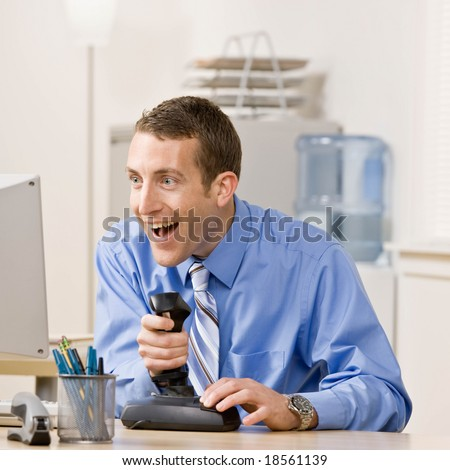 Excited businessman enjoying video game on computer at desk