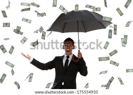 Excited businessman holding hand out in a money rain storm - stock photo