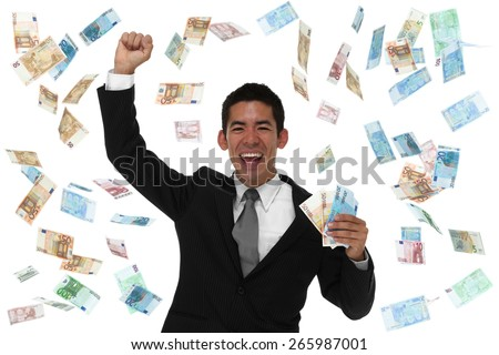 Excited businessman in a money rain storm with hand up in the air. - stock photo